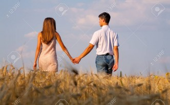Young couple walking through  wheat field